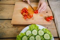 Na drewnianym stole, kobiety knifes reżim czereśniowi pomidory na plasterkach dla jarzynowej sałatki Fotografia Stock