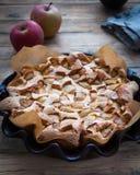 Na drewnianym stole w formie dla piec jabłczanego kulebiaka od lotniczego ciasta świeżych jabłek i zdjęcie royalty free