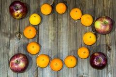 Na drewnianym tło zmroku czerwoni jabłka i żółci tangerines - fotografia stock