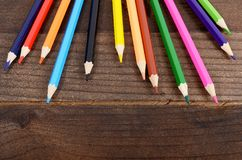 Na drewnianym tle barwioni ołówki obraz stock