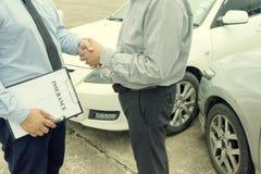 Na drogowego wypadku samochodowego asekuracyjnym agencie egzamininuje carcrash Fotografia Stock
