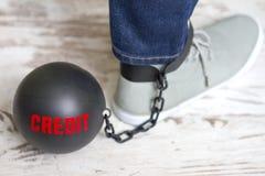 Na escravidão do conceito do crédito com a bola de metal na corrente e no pé Fotografia de Stock