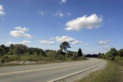 Na estrada com árvores e nuvens imagens de stock