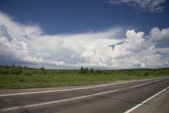 Na estrada com nuvens Fotos de Stock Royalty Free