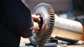 Na fábrica, um homem instala um rolamento na engrenagem vídeos de arquivo