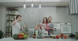 Na família da cozinha que passa uma boa estadia que joga junto com bolhas e que dança antes de fazer o café da manhã saudável vídeos de arquivo