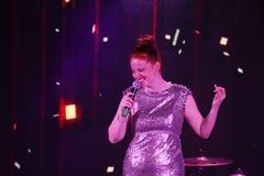 Na fase, na hortelã do grupo da PNF-rocha dos músicos e no cantor Anna Malysheva Canto glam dirigido vermelho da menina da rocha Foto de Stock