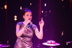 Na fase, na hortelã do grupo da PNF-rocha dos músicos e no cantor Anna Malysheva Vermelho Canto glam dirigido vermelho da menina  Imagens de Stock Royalty Free