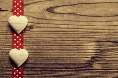 Na fita vermelha do às bolinhas, chocolate coração-dado forma - fundo de madeira Foto de Stock Royalty Free