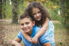 Na floresta do outono, uma irmã encaracolado pequena abraça delicadamente seu o Foto de Stock Royalty Free
