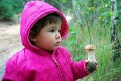 Na floresta, a menina está guardarando um boleto do cogumelo. Imagem de Stock
