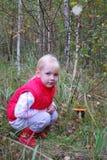 Na floresta, a menina que senta-se perto de um cogumelo. Imagem de Stock