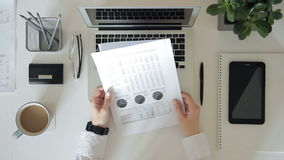 Na górze руки белой таблицы человеческой держа бумагу с диаграммами акции видеоматериалы