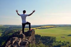 Молодой человек na górze утеса Стоковое Изображение