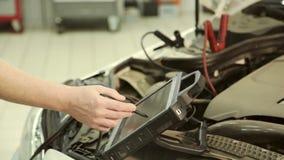 Na garagem um mecânico que usa o computador conduz o ajustamento do motor da microplaqueta vídeos de arquivo
