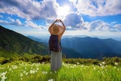 Na gazonie biali kwiaty modniś dziewczyna zostaje w długiej sukni, słomiany kapelusz z plecy workiem, cieszy się zmierzch Obraz Stock
