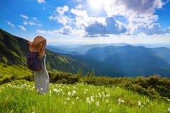 Na gazonie biali kwiaty modniś dziewczyna zostaje w długiej sukni, słomiany kapelusz z plecy workiem, cieszy się zmierzch Fotografia Royalty Free