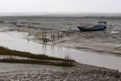 Na het eb, liep de boot op de getijde vlakke rivier van modder vast, Royalty-vrije Stock Afbeelding