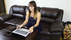 Na het werken aan laptop, zette het meisje een karaf met alcohol en een glas op de lijst stock footage