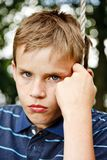 Na huśtawce chłopiec smutny przyglądający obsiadanie Obrazy Stock