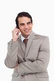 Na jego telefon komórkowy uśmiechnięty sprzedawca Fotografia Royalty Free