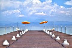 Na jetty przy Jeziornym Gardą jarzy się świecących barwiących sunshades fotografia stock