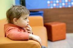 Na kanapie chłopiec obsiadanie Obrazy Royalty Free