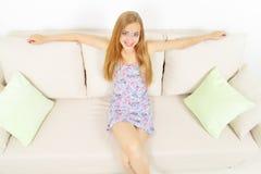 Na kanapie dziewczyny uśmiechnięty obsiadanie Obrazy Royalty Free