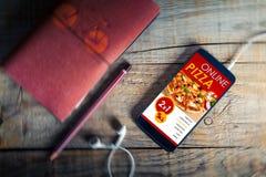 Na kreskowym pizza sklepie w telefonu komórkowego ekranie nad drewnianym biurkiem, obraz stock