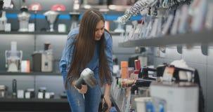 Na loja de dispositivos, a mulher dos dispositivos de cozinha escolhe um misturador em suas mãos e considera o projeto e vídeos de arquivo