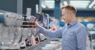 Na loja de dispositivos, o técnico da cozinha escolhe o misturador em suas mãos e considera o projeto e filme