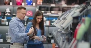 Na loja de dispositivos, um casal feliz, um homem e uma mulher na roupa ocasional, escolhem um misturador para comprar, perto video estoque