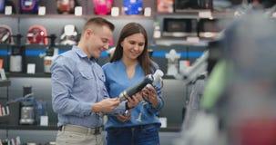 Na loja de dispositivos, um casal na roupa di?ria escolhe um misturador para a compra vendo e guardando filme