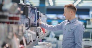 Na loja de dispositivos, um homem em uma camisa escolhe um misturador comprar vendo e guardando o dispositivo vídeos de arquivo