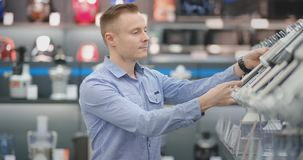 Na loja de dispositivos, um homem em uma camisa escolhe um misturador comprar vendo e guardando o dispositivo filme
