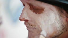 Na mężczyzna ` s twarzy stawiać dalej białego makijaż zbiory wideo