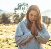 Na menina da manhã fechado seus olhos, rezando fora, as mãos dobraram-se no conceito da oração para a fé, espiritualidade, concei foto de stock