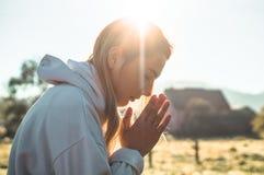 Na menina da manhã fechado seus olhos, rezando fora, as mãos dobraram-se no conceito da oração para a fé, espiritualidade, concei fotografia de stock