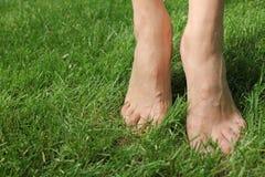 Na menina descalça da grama verde A menina está estando na ponta do pé Fotografia de Stock Royalty Free