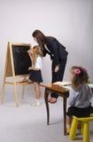 Na menina do quadro-negro com fôrmas de uma tração do tutor, uma outra menina que senta-se na tabela Foto de Stock Royalty Free