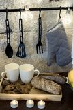 Na mesa de cozinha na frente de uma parede cinzenta concreta são os assobios brancos um a festão suporte de potenciômetro de susp foto de stock royalty free