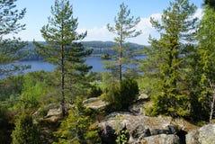 Na montanha há pinhos e abetos, grandes pedras, um lago sob a montanha, uma casa pequena na costa da baía fotografia de stock royalty free