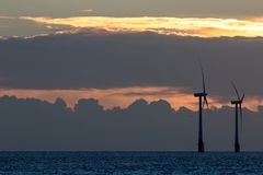 Na morzu farm wiatrowych turbin sylwetka przy wschód słońca lub zmierzchem zdjęcia royalty free