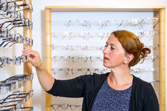 Na mulher da loja do ótico que seleciona vidros novos fotografia de stock
