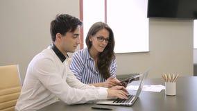 Na mulher do escritório com a tabuleta e o homem que trabalham na frente do portátil vídeos de arquivo