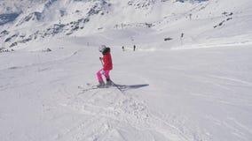 Na mulher do novato do movimento o esquiador abaixo do longo gerencie sobre a inclinação de uma montanha filme