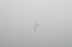 Na névoa de um homem asiático em um barco que flutua no rio Fotos de Stock Royalty Free