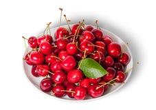Na odgórnych słodkich wiśniach z liściem na bielu talerzu Fotografia Royalty Free