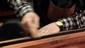 Na oficina, um especialista aponta uma correia de couro Procedimento para a fabricação das correias de couro filme