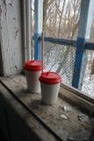 Na okno starzy dwa budynku papierowe filiżanki Zdjęcie Stock